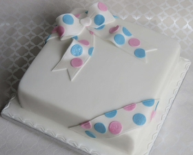 Baby reveal cake. Parcel cake -pink and blue spotted ribbon