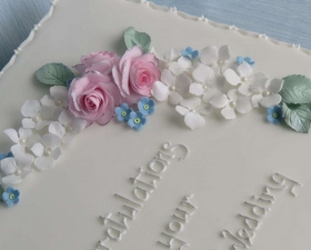 Crescent of roses, hydrangeas, and forget-me-not cake topper