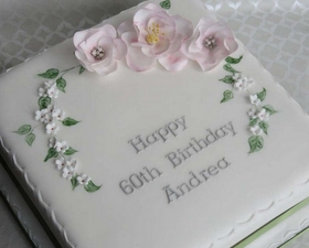 Crescent of open roses and white blossom cake